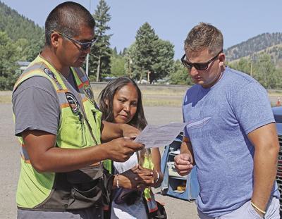 CSKT watercraft inspectors Wilbert Michel, Jr. and Kayla Gardipie check Casey Carnahan's paperwork