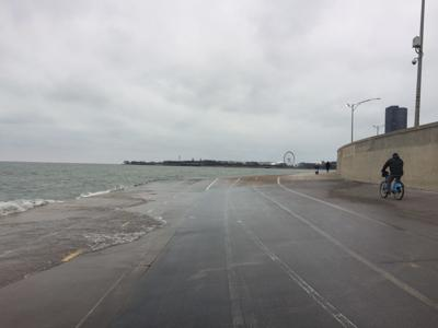Lake Michigan waves lap the Lakeshore Path, a popular thoroughfare for cyclists 1