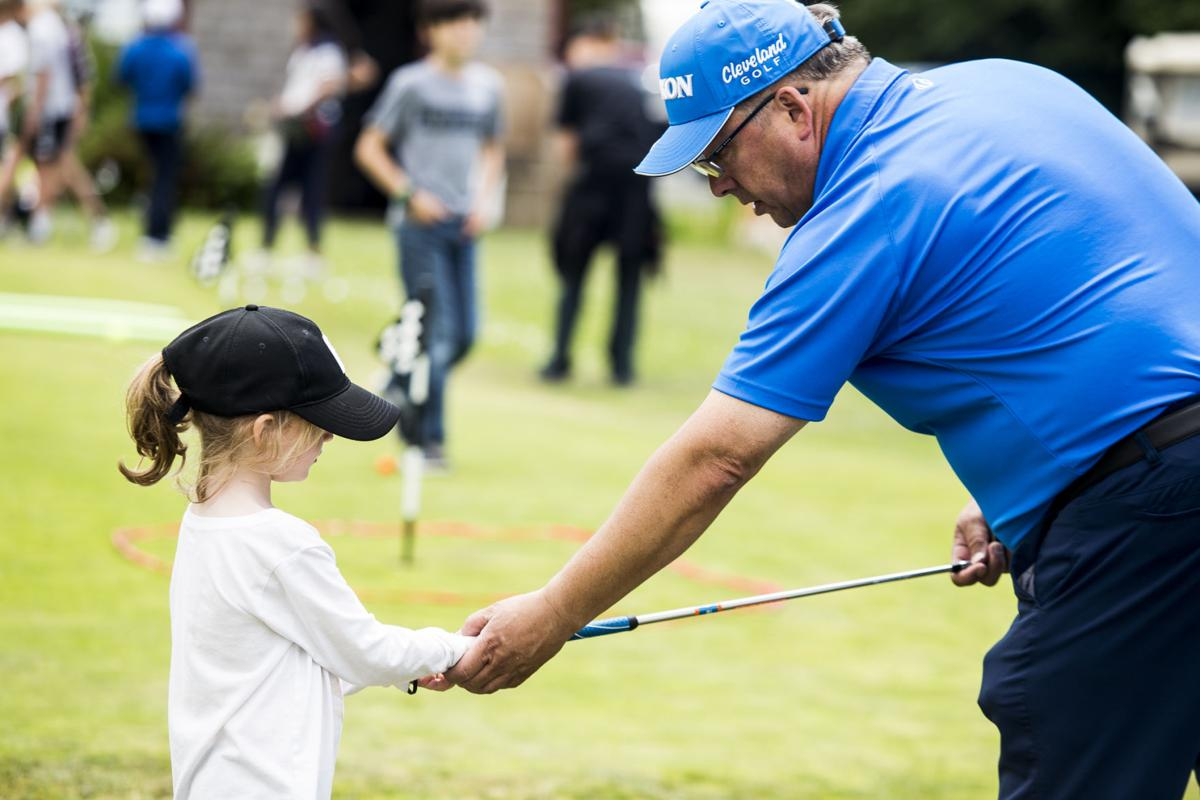 Doug Brown gives instruction on grip to a young golfer