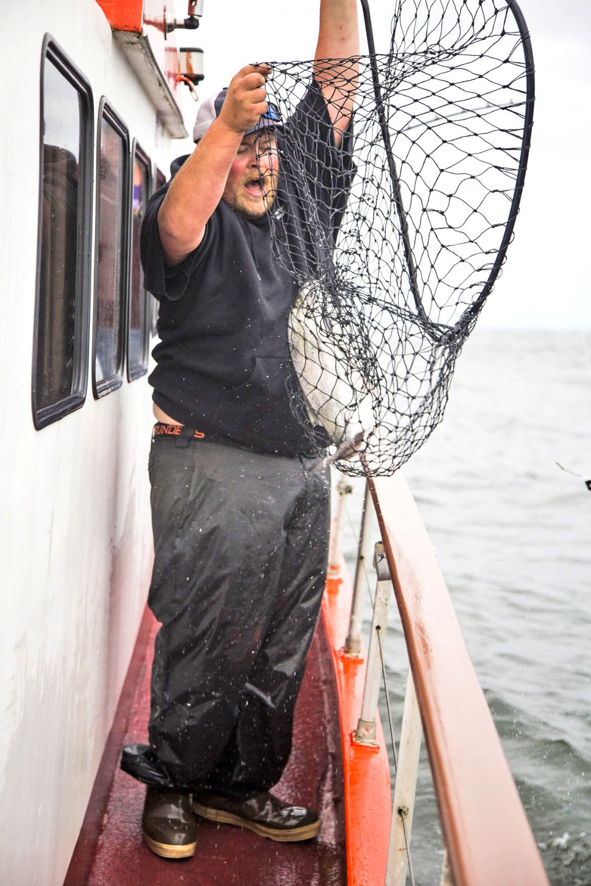 Deckhand Kevin Koski reacts to the first coho salmon