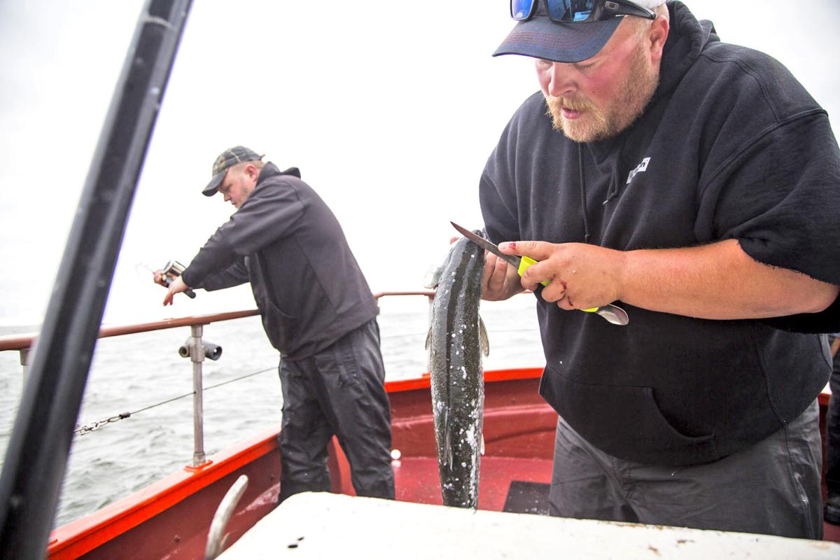 Deckhand Kevin Koski marks a keeper coho for a customer
