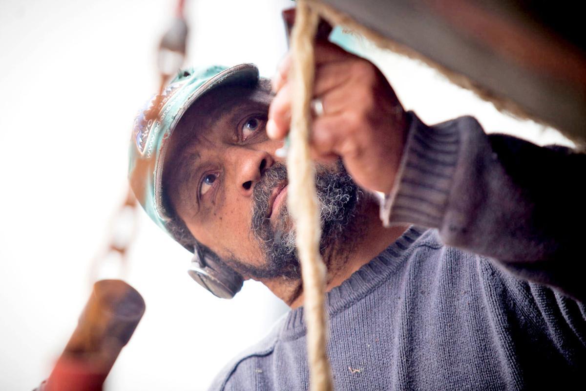 Shipwright Dana Linwood caulks a boat