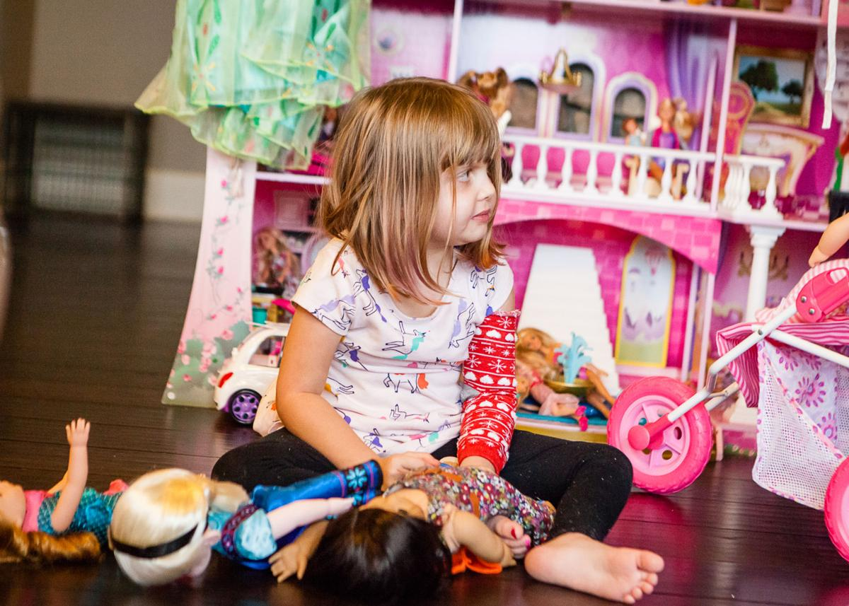 Four-year-old Dylan Harrel played with her dolls on Nov. 25. IThanks to intensive radiation treatments, she has regained some of her strength recently.