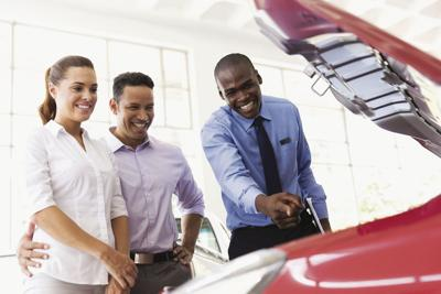 car salesman showing car engine to customers