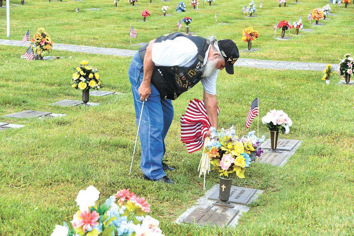 Vietnam Veterans put flags on graves at Hamblen Memory Gardens