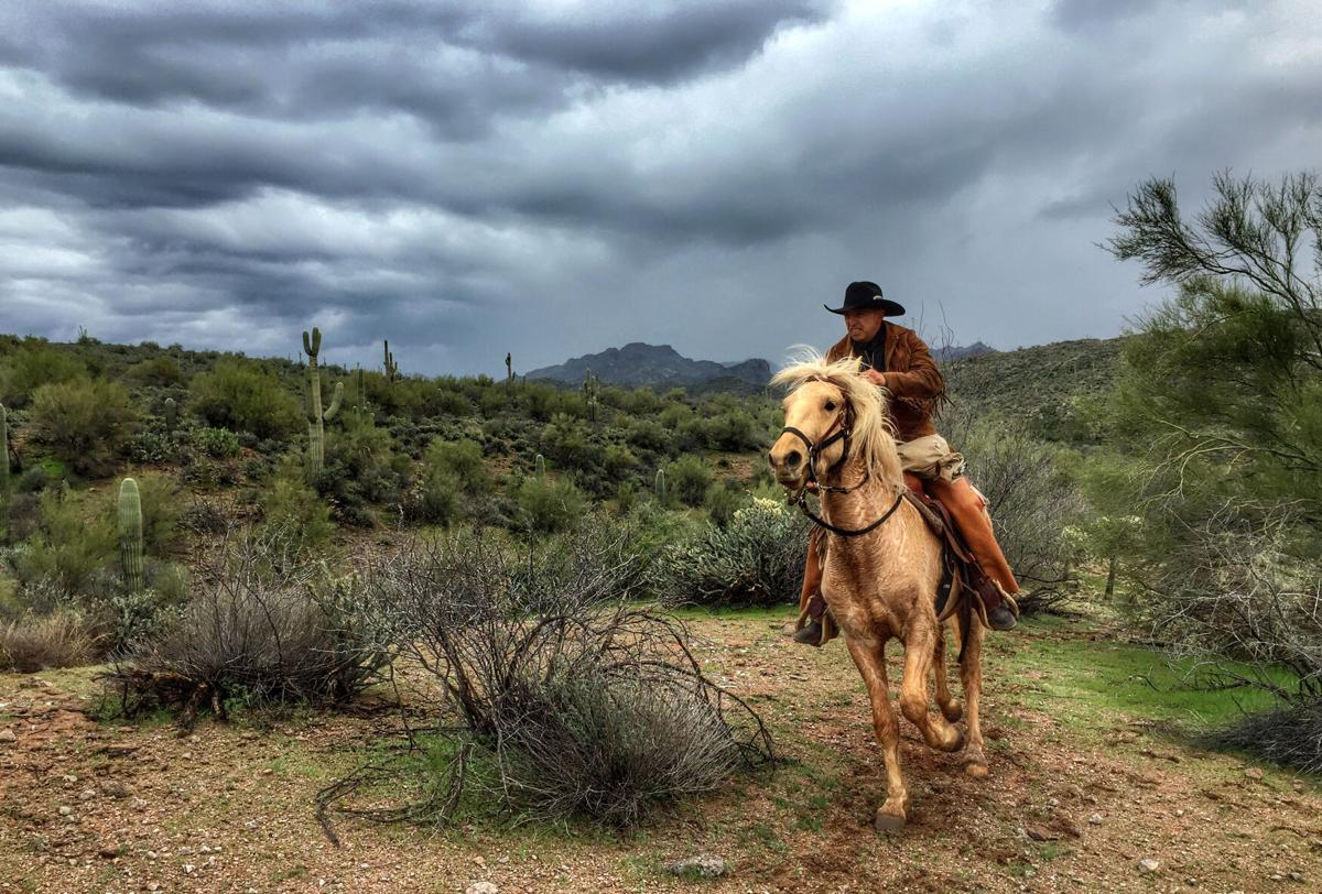 A rider from the Hashknife Pony Express gallops through the desert under stormy skies.