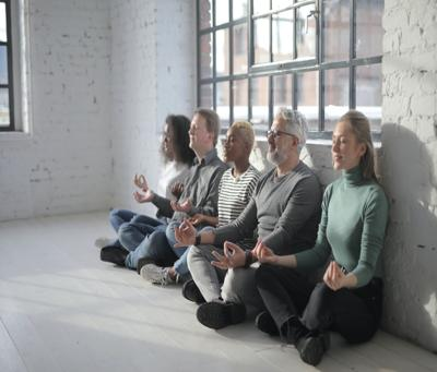 diverse group of colleagues having meditation together