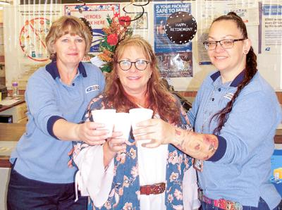 Postal clerks Diane Cochrell (left) and June Delgado toast Marty Wilkins' 30 years of service during her retirement celebration last Wednesday, Sept. 30.