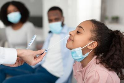 Doctor taking PCR test sample from potentially infected Black girl (copy)