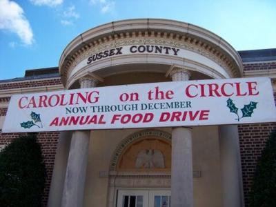 Caroling on The Circle food drive banner