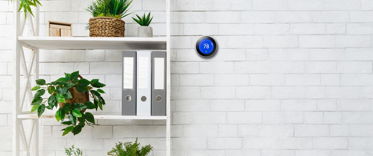 Nest thermostat, white bookshelf with plants and folders over wall