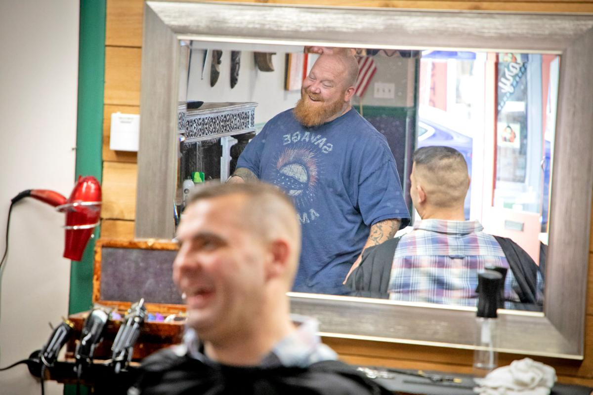 Barber Jacob Sullivan laughs as he interacts with a customer in early January