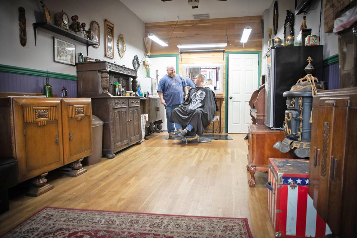 Victory Barbershop owner Jacob Sullivan chats with a customer