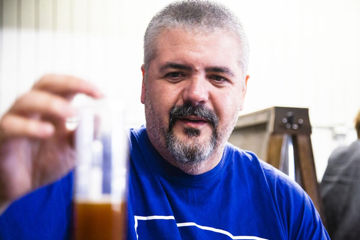 Ryan Porter observes the gravity level of the beer to monitor the fermentation process