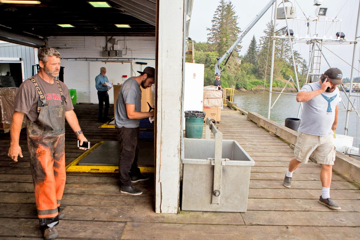 Commercial albacore fisherman Patrick Roelle, left, and Ilwaco Landing Fishermen co-owner Mike Shirley, right, at walk the docks at Ilwaco Landing in August