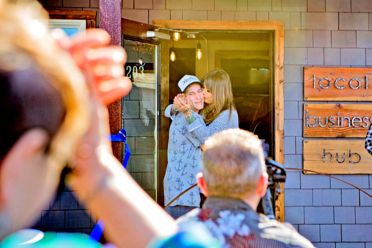 Casey and Gail embrace after a ribbon-cutting ceremony in front of cheering family and friends