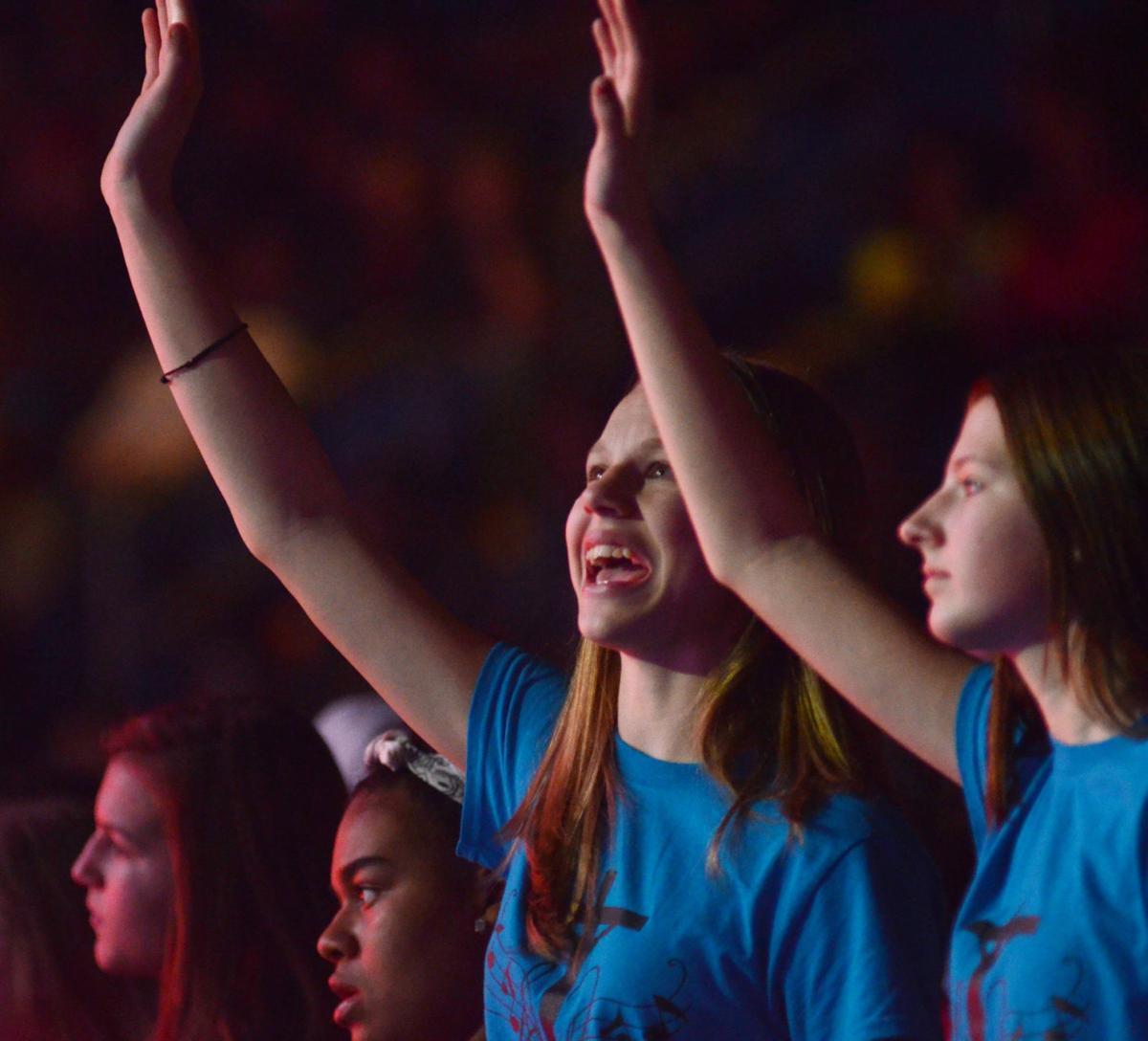 A fan raises her hands in praise