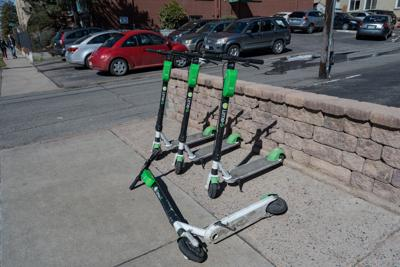 E-scooters on a side walk in Denver's Capitol Hill Neighborhood.  4 scooters, 3 standing 1 knocked down.