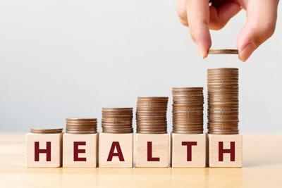 Hand putting coins on stack stair as step growing growth and wooden cube block with word HEALTH. Investment health and insurance fund concept