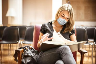 student with face mask in the library