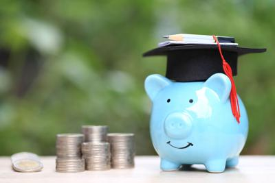 Saving money for education concept, Growing stack of coins money with graduation hat on piggy on nature green background