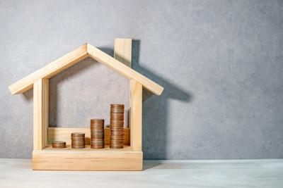 Coins stacked in wooden house frame on table. Home mortgage loan rate. Saving money for future retirement. Real estate investment or property ladder concept. Housing project for construction business