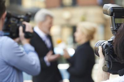 Photographer Taking Pictures Of Female Journalist Interviewing B