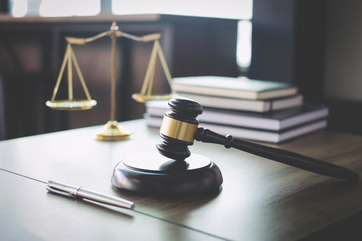 Scales of justice and Gavel on wooden table and Lawyer or Judge working with agreement in Courtroom, Justice and Law concept