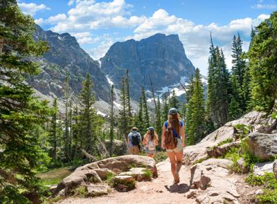 Family hiking on summer vacation in Colorado mountains.