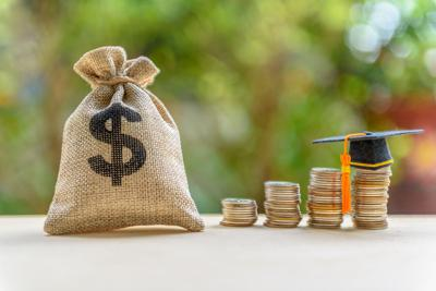 Education expense or student loan for post secondary education concept : Dollar bag, graduation cap on row of coins on a table, depicts loan or money designed to help students pay for associated fees