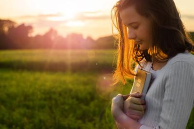 Christian teenage girl holds bible in her hands. Reading the Holy Bible in a field during beautiful sunset. Concept for faith, spirituality and religion