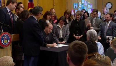 Gov. Jared Polis signs an order creating the Office of Saving People Money on Healthcare