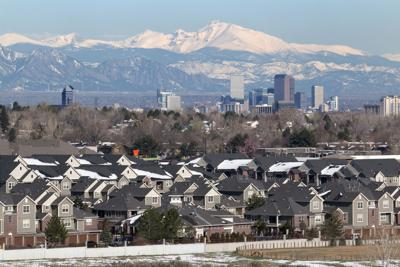 Wintery homes downtown Denver Colorado skyscrapers with Rocky Mountains