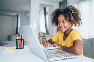 Schoolgirl studying with video online lesson at home.