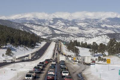 Traffic jam westbound I-70 highway with snow covered mountains Colorado