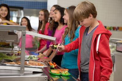 Middle school students choosing healthy food in cafeteria lunch line