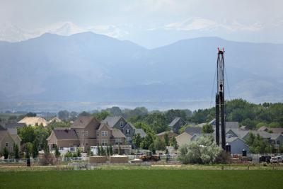 Natural gas drill rig with homes and Colorado Rocky mountains