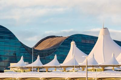 The Westin Denver International Airport looms over the white tented roof of the airport's main terminal.