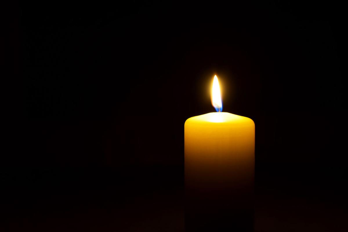 One yellow candle flame  burning in darkness