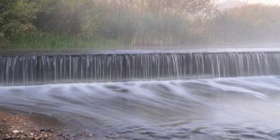 Mornig fog over a river dam