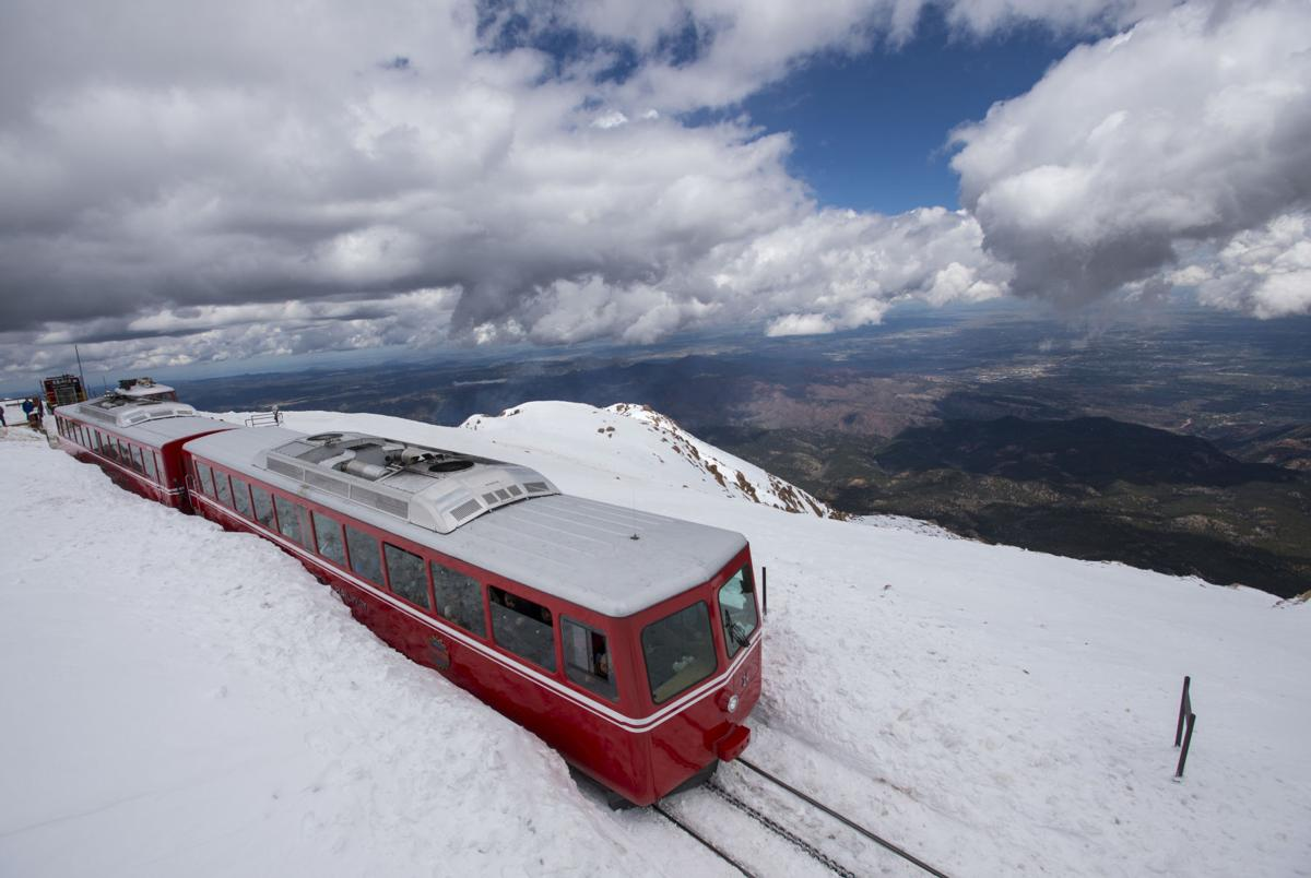 The Pikes Peak Cog Railway train leaves the summit as another storm approaches Friday, May 29, 2015. The highway is open to mile marker 15, the Double Cut between Glen Cove and Devil's Playground. Under ideal conditions crews hope to have the road open to Devil's Playground early next week and to the 14,115-foot summit in about 10 days, but more snow is in the forecast. (The Gazette, Christian Murdock)