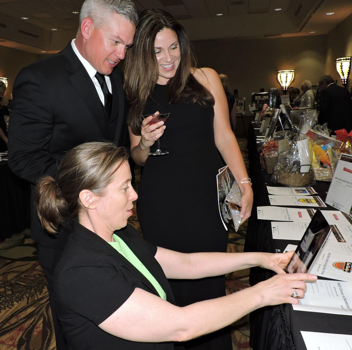 Junior Achievement 25th annual gala: Tara McGowan shows the real-life criminals on the 19 Crimes Australian wine labels to Angela Micheletti and Aaron Anderson. 050518 Photo by Linda Navarro