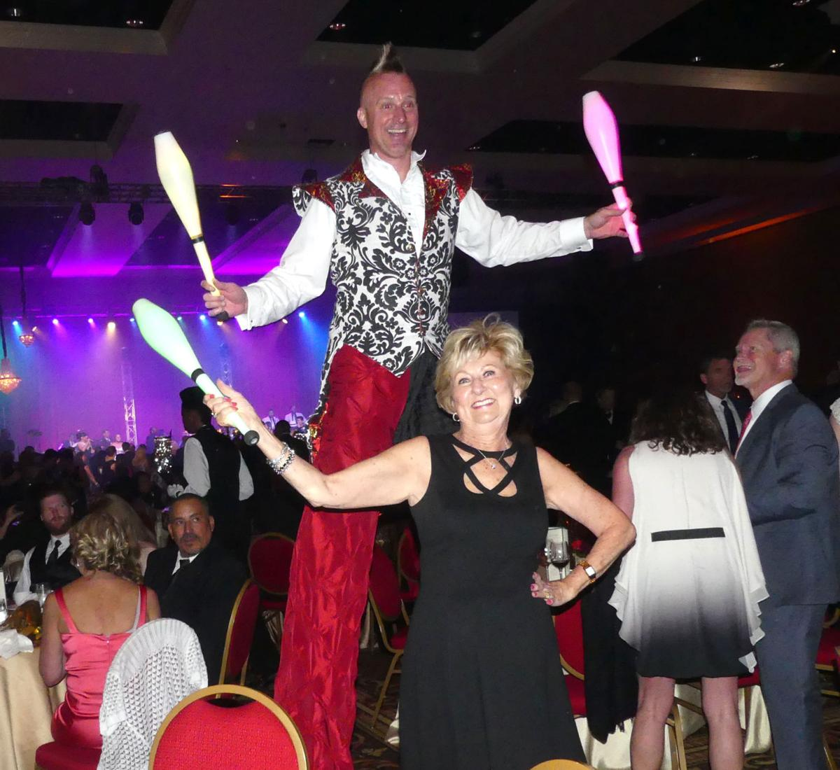 Broadmoor 100th Anniversary Gala: Char Anneler learns a little juggling action from a stilt walker, one of the entertainers. 060218 Photo by Linda Navarro