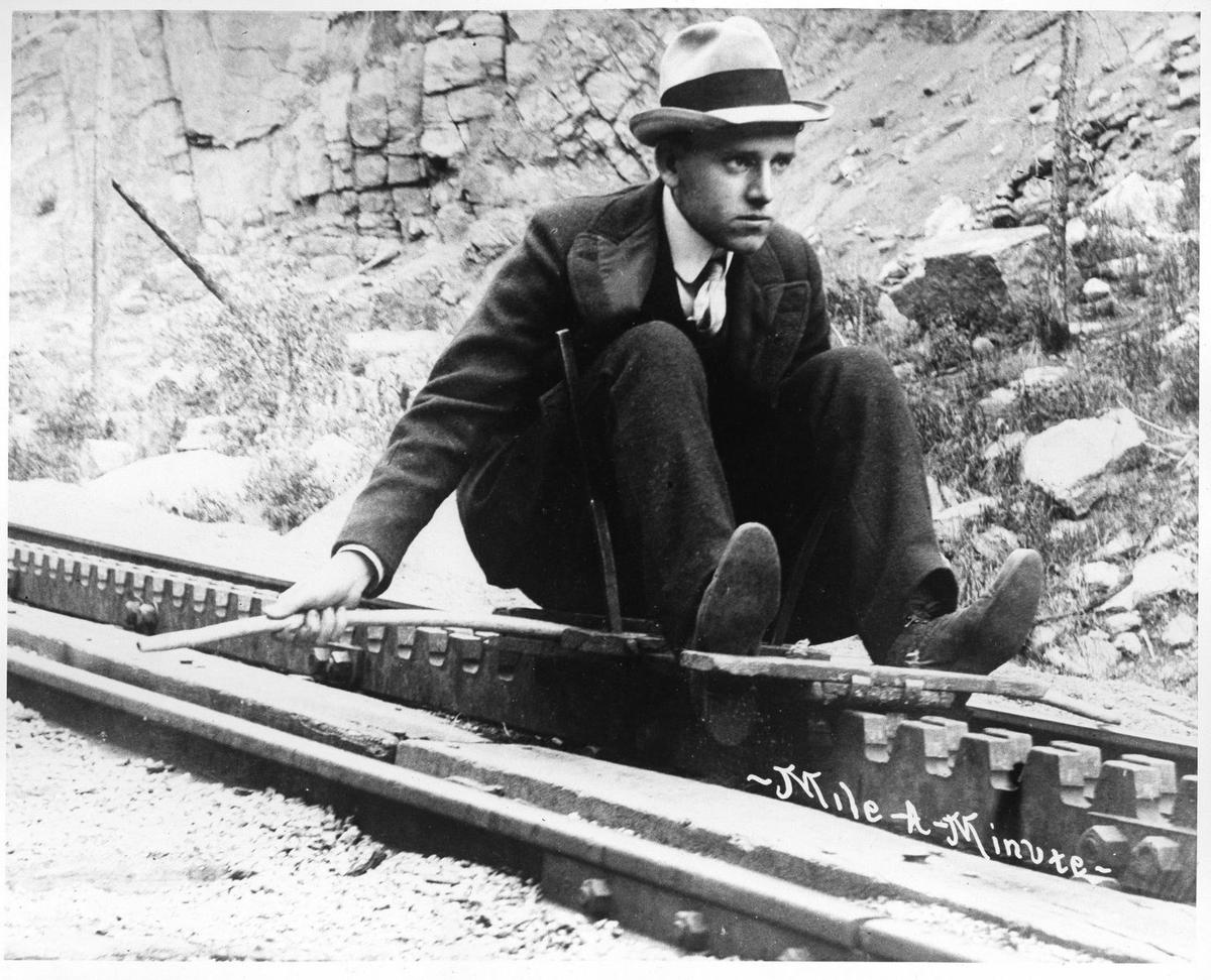 """Go-Devils Orrie W. Stewart, wearing a suit, tie and hat, """"coasts"""" down the Cog Railway track on a personal sled, or """"go-devil,"""" in an undated photo. Orrie and his brother Ben founded the Stewart Brothers Commercial Photography business in Colorado Springs. Photo by Stewarts Commercial Photographers, Pikes Peak Library District, 013-2386"""