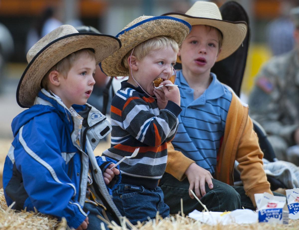Cameron Johnson, 2, center, eats his pancakes while his brothers Blake, 4, left, and Aidan, 7, listen to the live music Wednesday, June 17, 2015, during the annual Western Street Breakfast in downtown Colorado Springs celebrating the Pikes Peak or Bust Rodeo in July. (The Gazette, Christian Murdock)