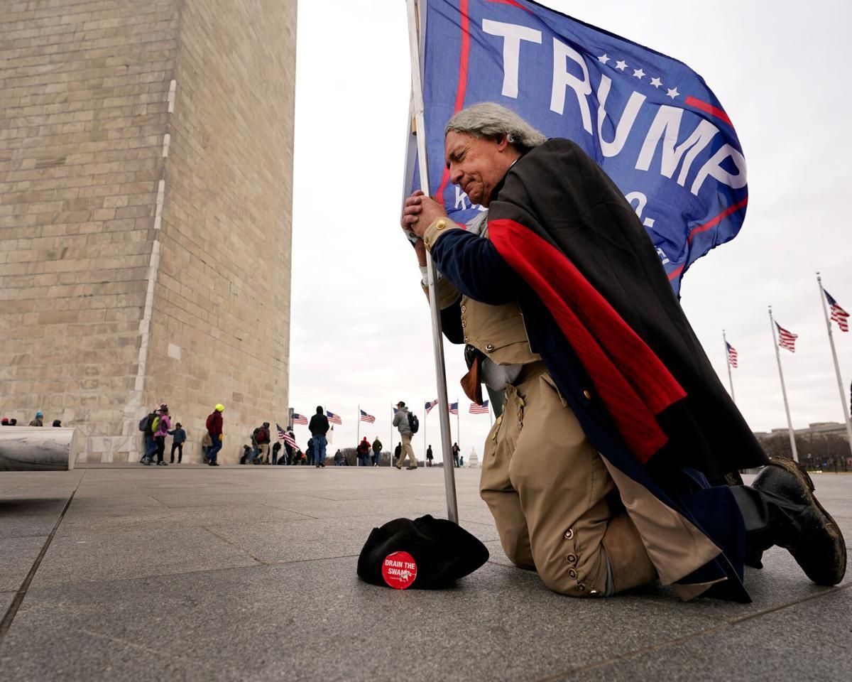 A man dressed as George Washington kneels and prays