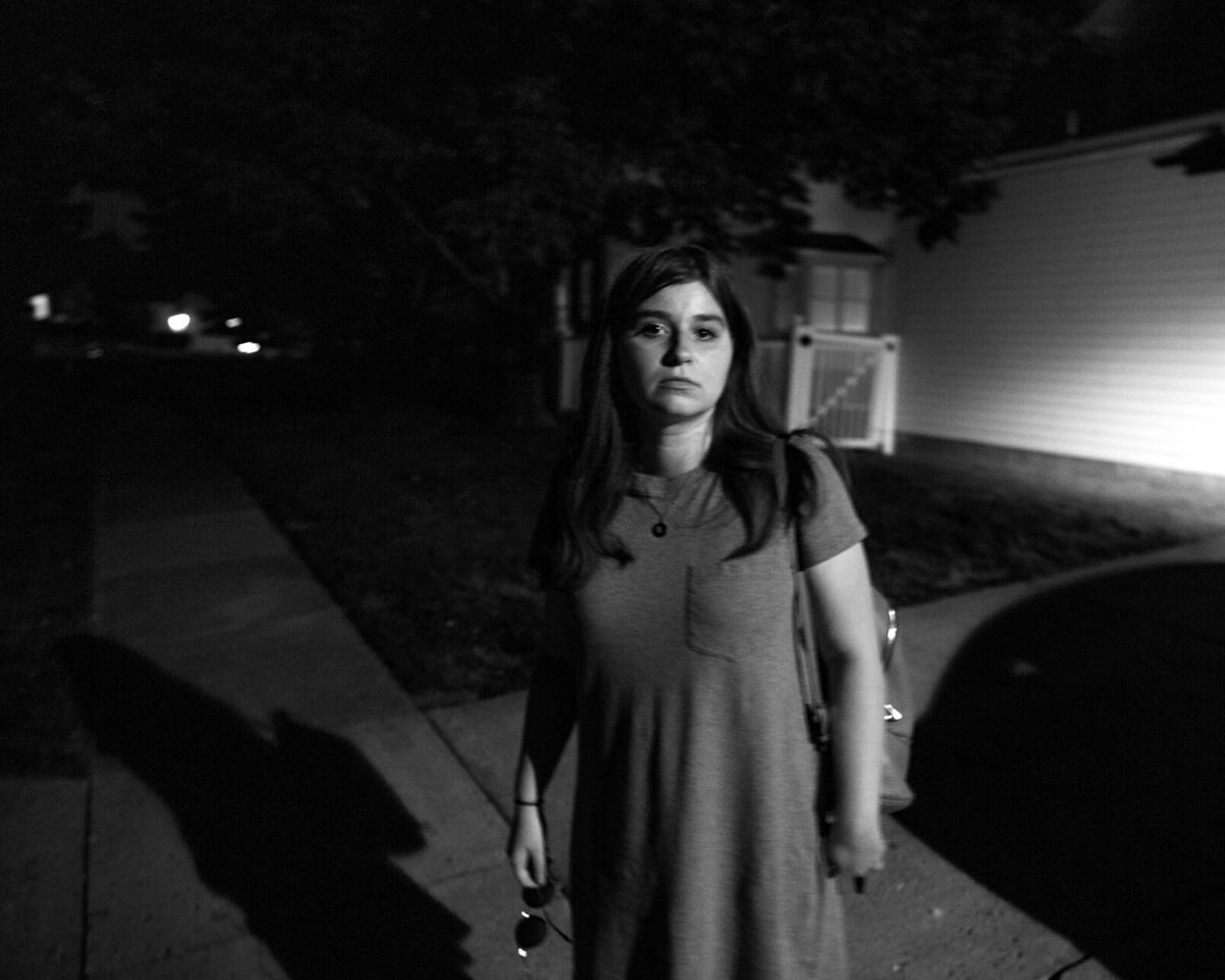Emma stands outside her parents' home