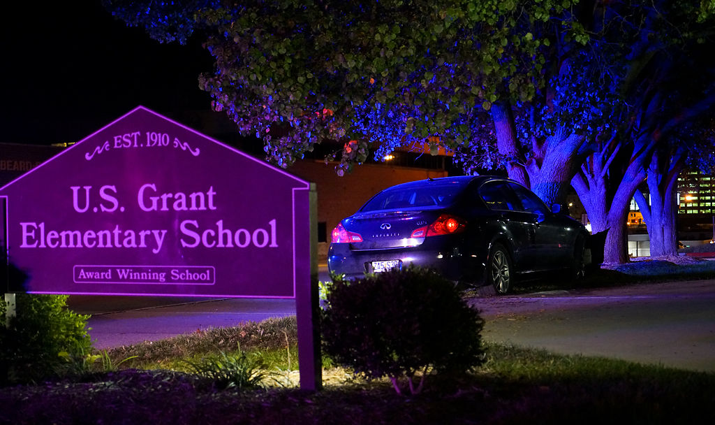 A car lies abandoned after crashing into a tree in front of U.S. Grant Elementary School by the intersection of Broadway and South Garth Avenue