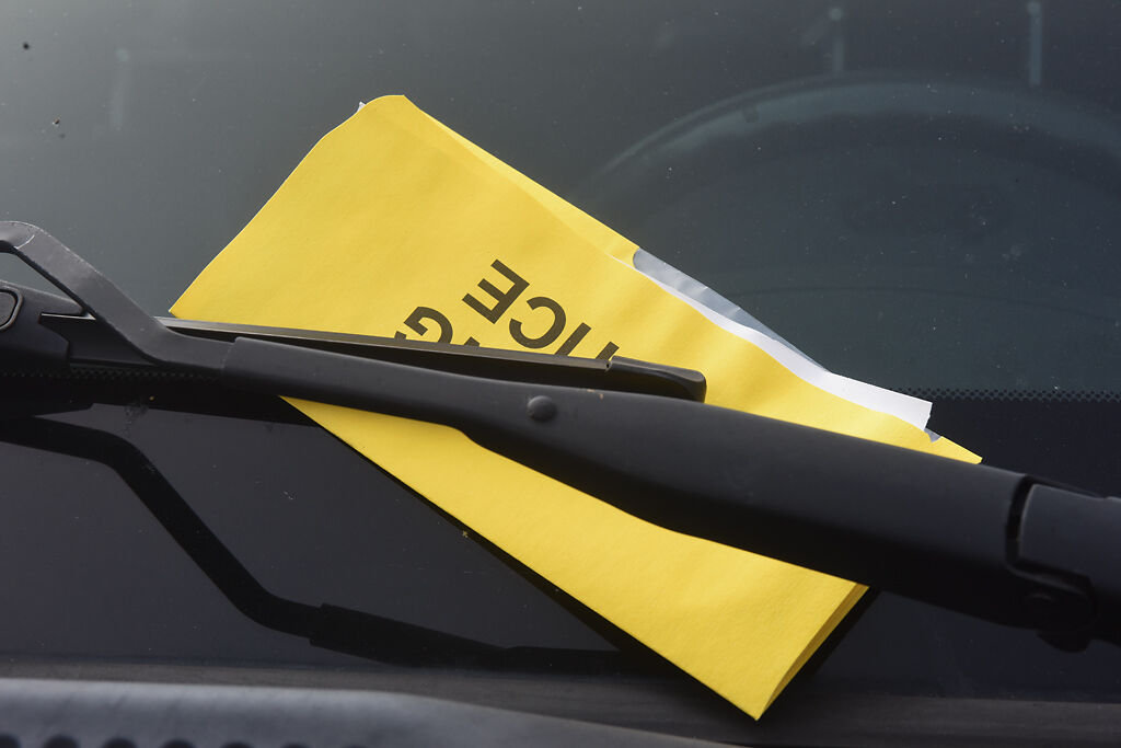 A parking ticket sits tucked under a windshield