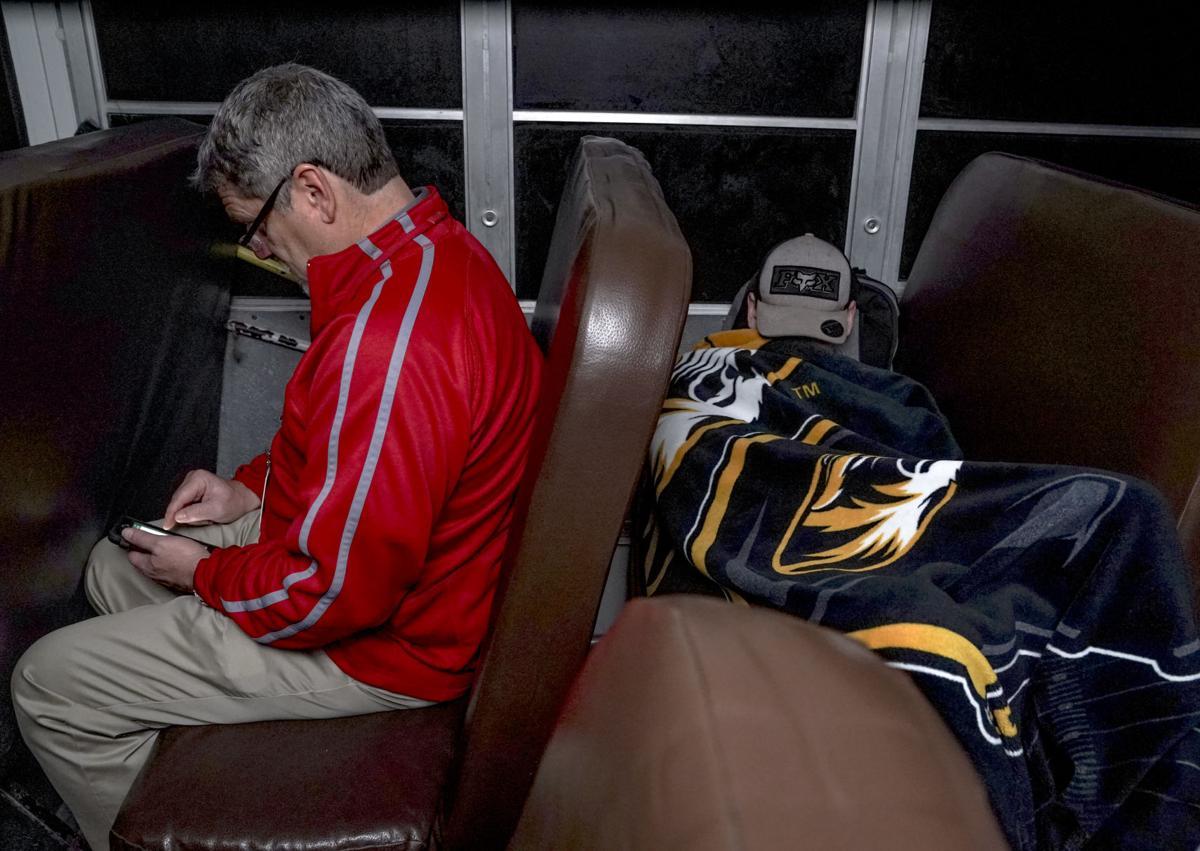 Dan Bachmeier, left, plays Garden Scape on his phone while Kevin Raines sleeps